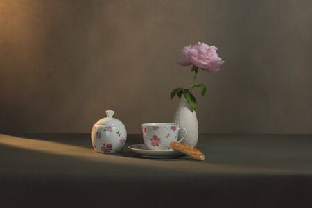 Tea cup with saucer and cookie, sugar bowl and white vase with peony on a table in a grey room in morning sunlight.