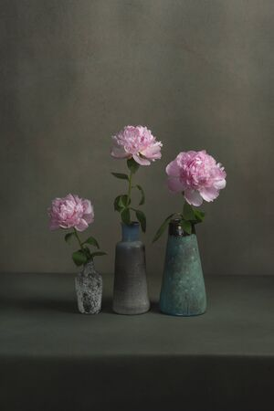 Three vintage pottery vases with pink peonies on a table in a grey room.