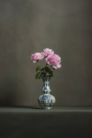 Pink peonies in a delft blue vase on a table in a grey room. Foto de archivo