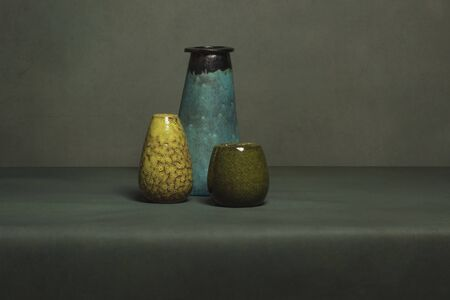 Blue, yellow and green vintage vase on a grey table in front of a gray wall.