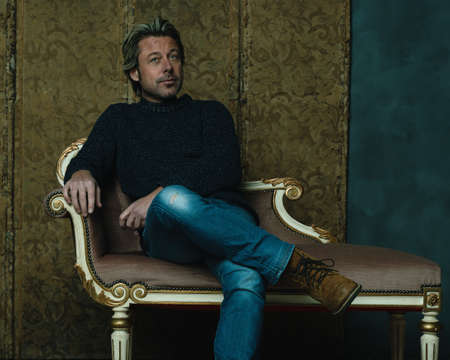 Contemporary man in sweater and jeans sitting on vintage sofa in room.