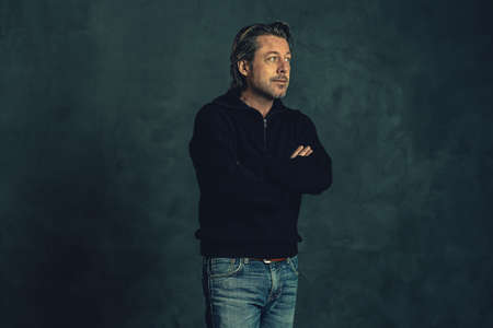 Man with stubble beard in black woolen sweater against gray wall. Imagens