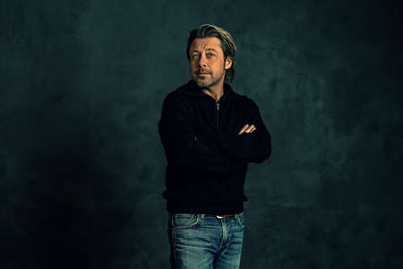 Man with stubble beard in black woolen sweater against gray wall.
