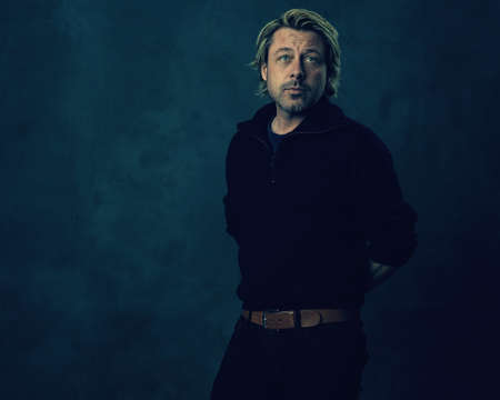 Relaxed blonde man with stubble beard in black wool sweater and jeans in front of a dark wall. Imagens