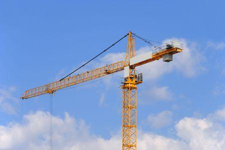 De gele bouw kraan op een hemel achtergrond. Stockfoto