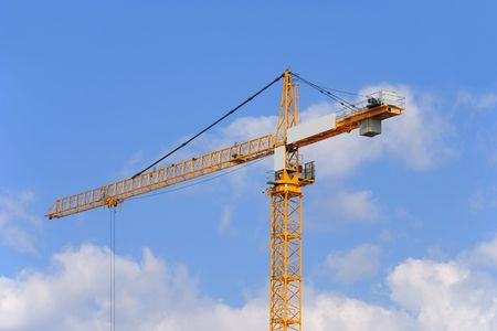 The yellow construction crane on a sky background.
