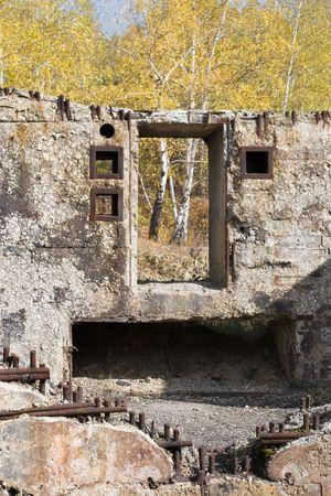 Beschadigde betonnen gebouw tegen de herfst bomen  Stockfoto