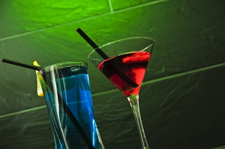 A red cocktail and a blue longdrink on a green background