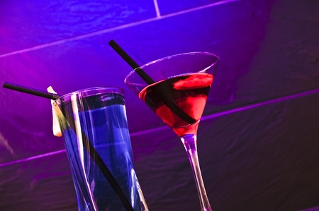 A red cocktail and a blue longdrink on a purple background Stock Photo