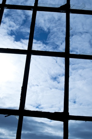 crossbars: Broken windows with glazing bars with a blue sky in the background