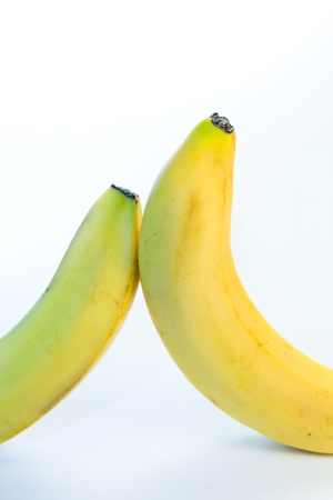 Two bananas are inclined towards each other on a white background Stock Photo
