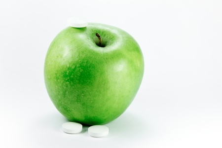 A granny smith apple with a three pills on a white background Stock Photo