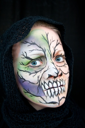 colleen: Crazy Halloween face painting in green, blue and black on a young woman