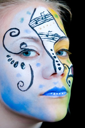 young woman with blue, yellow and black face paint with a very intense gaze Stock Photo