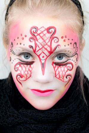 colleen: young woman with pink, red and black face paint with a very intense gaze Stock Photo