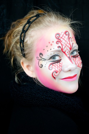 young woman with pink, red and black face paint with a very intense gaze photo