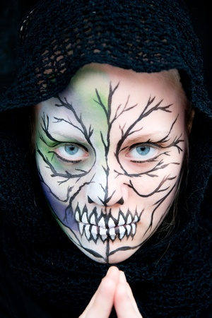 stage makeup: young woman who looks dangerous and crazy with Halloween face painting Stock Photo