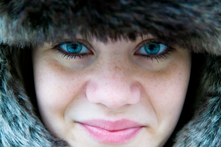 incredibly cute girl with freckles with a fur hat, close-up