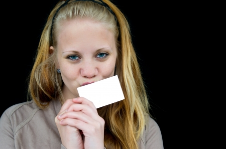 girl kissing unwritten white piece of paper and looking straight into the camera