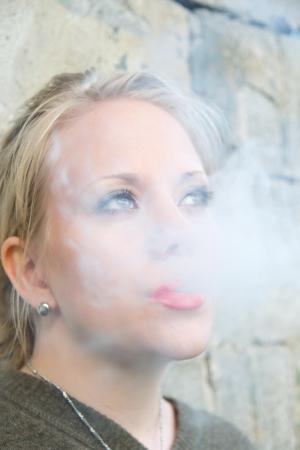 cigarette smoke: giovane e bella donna dietro una cortina di fumo di sigaretta