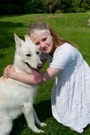 white shepherd dog: ragazza che abbraccia un cane bianco pastore seduto su un prato