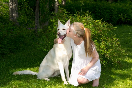 girl who kisses a dog, a beautiful summer day in nature Stock Photo