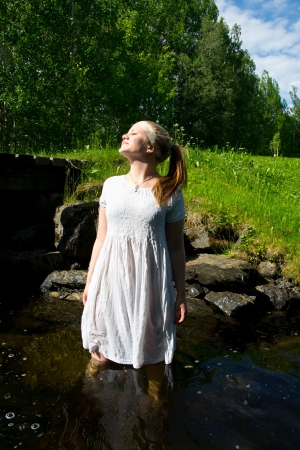 beautiful girl in white dress standing in the water and enjoying the sun