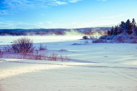 winter landscape of icy and snowy lake with mist over and a blue sky in the background photo