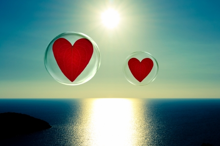 Two hearts in bubbles that float above a sparkling sea with the sun in the background