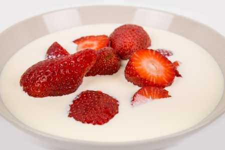 red ripe strawberries in a bowl with the cream and milk on a white background Stock Photo