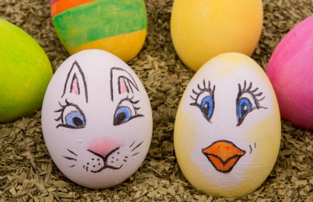 two eggs with motifs of an Easter bunny and chicken with multi colored eggs in the background photo
