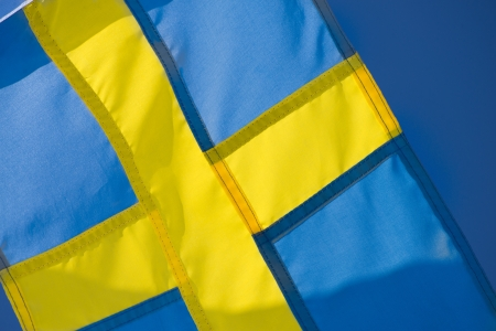 Swedish flag, yellow and blue, a symbol of Sweden with a blue sky in the background Stock Photo - 18792991