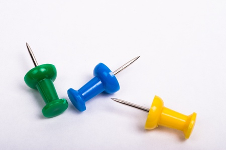 yellow thumbtacks: three thumbtacks, one green, one yellow and one blue on a white background Stock Photo