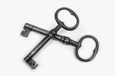 two great old well-used iron keys on a white background photo
