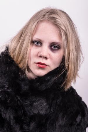 mujer golpeada: mujer golpeada con un ojo negro visualizaci�n proporcionadas directamente a la c�mara con un fondo blanco detr�s Foto de archivo