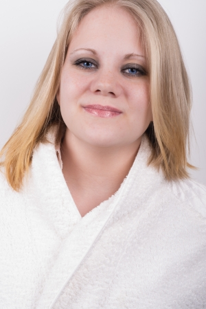 cut fresh young woman in a bathrobe in a spa with a white background behind her