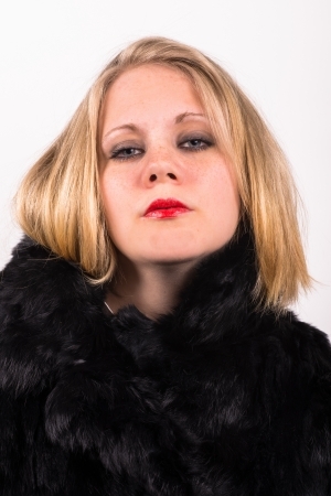saucy young attractive woman in a black fur jacket with a white background photo