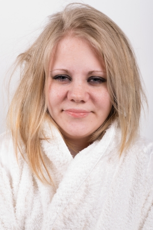 young female very tired sleepyhead in a white robe and a white background Stock Photo