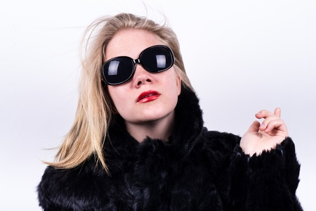 snobbish upper class girl in dark sunglasses, red lipstick and fur pointing behind hem on a white background