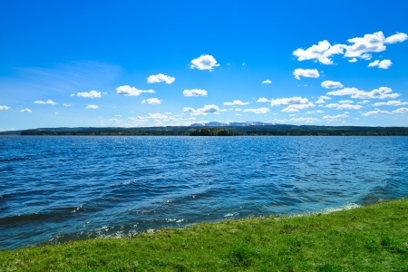 summer picture of lawn, lake, mountains and sky on a sunny day
