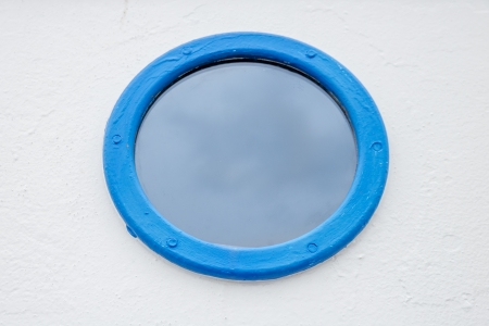 round blue painted window to a cabin of a boat