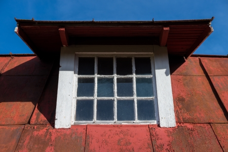 dormer: Dormer window on old ceiling with peeling red paint