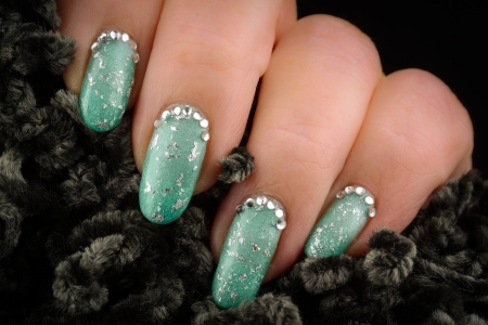Green nails with glitter and rhinestones on a dark background