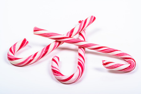 three twisted red and white candy canes on a white background Stock Photo