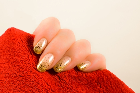 hand with gold nails holding a red towel on a white background