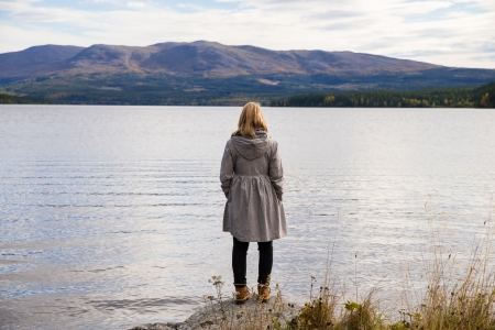 alone thinking woman standing on a stone and looking out over a beautiful mountain landscape Stock Photo