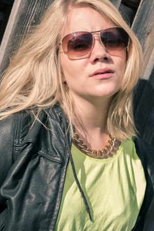 young female model with wind in her hair with sunglasses and leather jacket photo