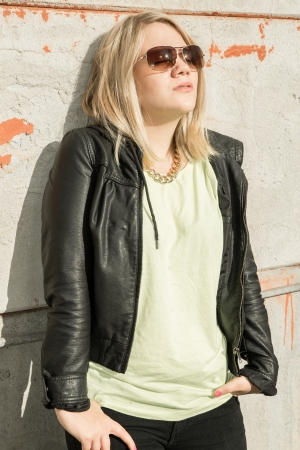 young woman hanging out and enjoying the sun against a wall with her eyes closed behind the sunglasses Stock Photo