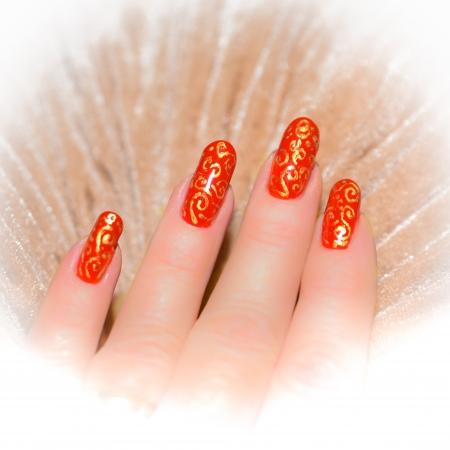 mano con las uñas de color rojo con el patrón oro sobre un fondo de color beige