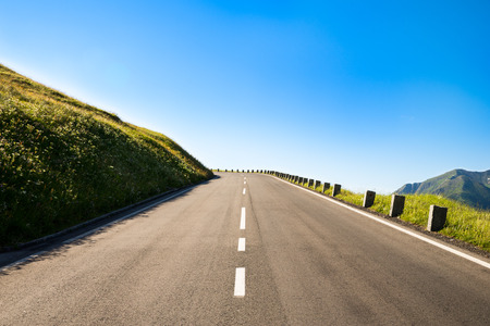 empty country road with a sharp left curve in the brow of a hill in the mountainous area photo